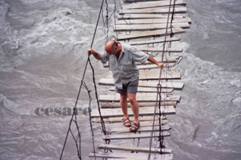 PAKISTAN Cesare with the Patagonia Stand Up Sorts walking on one Tibetan bridge over the Indo River